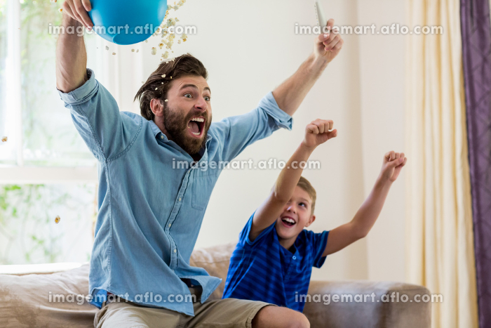 Excited father and son watching televisionの販売画像