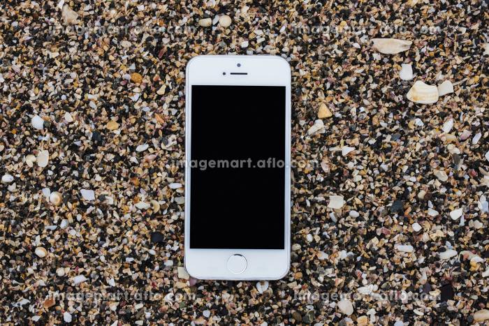 砂浜に置かれたスマートフォンの販売画像