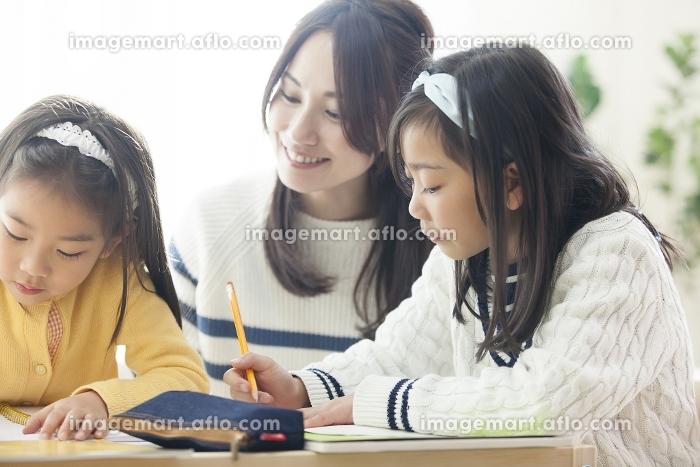 子供の勉強を見る母親の販売画像