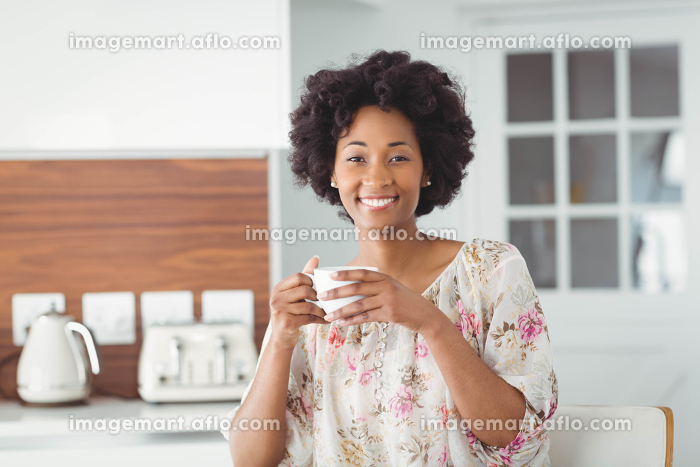 Portrait of smiling woman holding white cupの販売画像