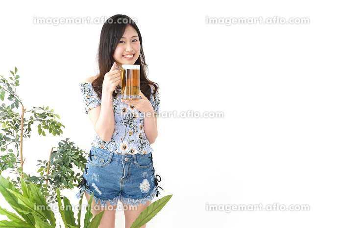 ビアガーデンでビールを飲む若い女性の販売画像
