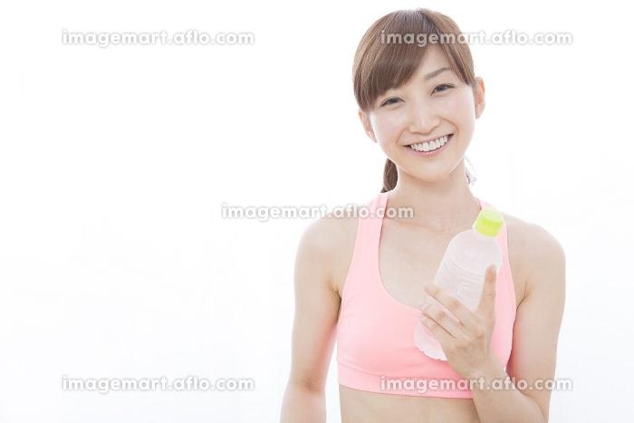 ペットボトルを持って微笑む女性の販売画像
