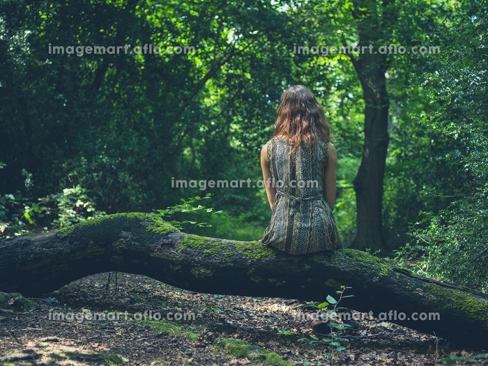 A young woman is sitting on a log in a clearing in the forestの販売画像
