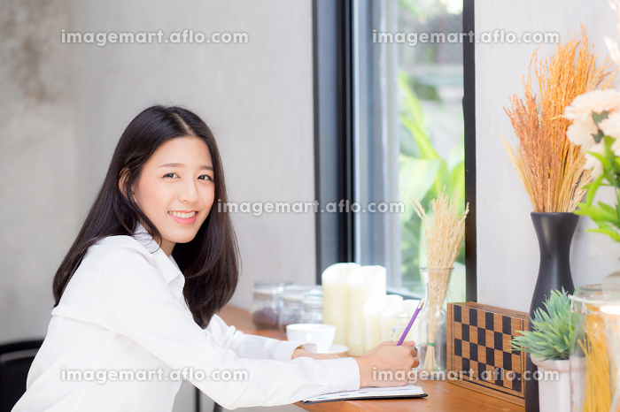Beautiful business asian young woman writing on notebook on tablの販売画像