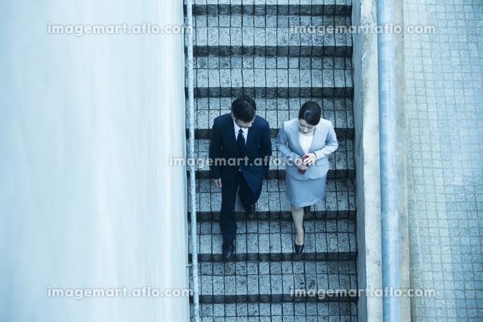 階段を下るビジネスウーマンとビジネスマン