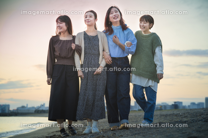 夕暮れの中、寄り添って海沿いを歩く女性4人の販売画像