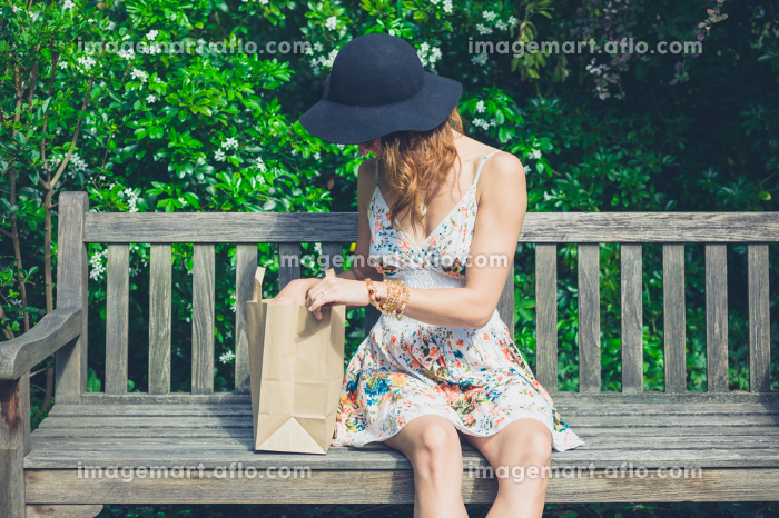 A young woman is sitting on a bench in a park and is looking at the content of a paper bag on a sunny day in the summerの販売画像