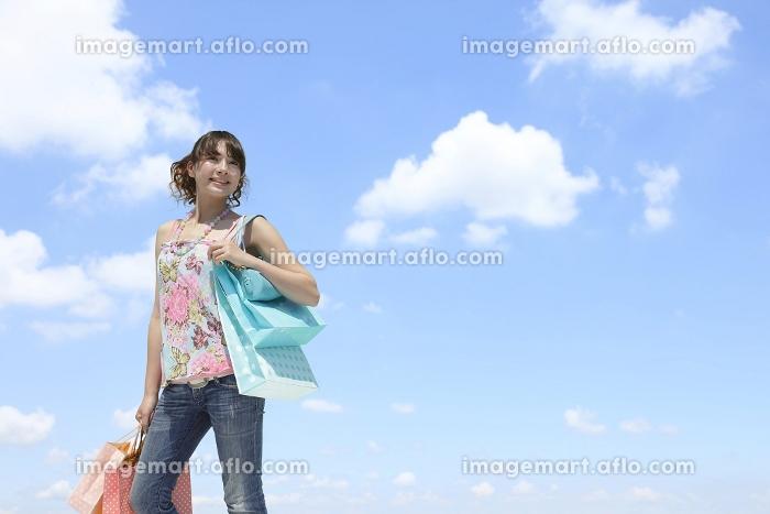 青空の下ショッピングを楽しむ若い女性の販売画像