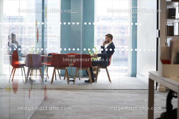 Young businessman using phone in an office meeting room