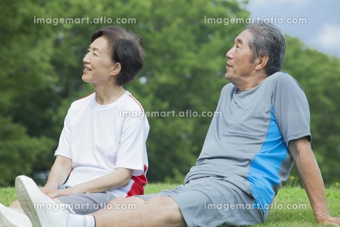 芝生に座る夫婦の販売画像
