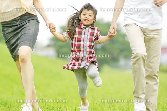 両親と手をつないでスキップする女の子の販売画像