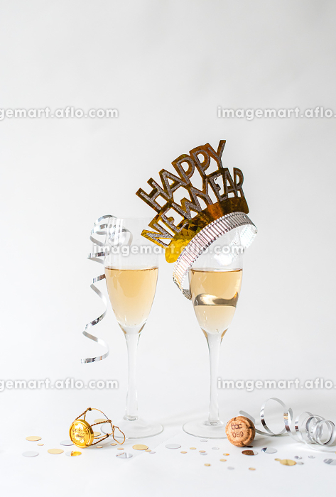 Glasses of champagne and Happy New Year hat on white background.の販売画像