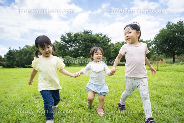 青空の下、元気に走る子供たちの販売画像