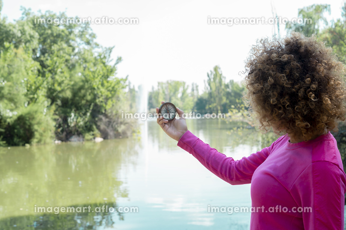 woman using her compass by the riverの販売画像