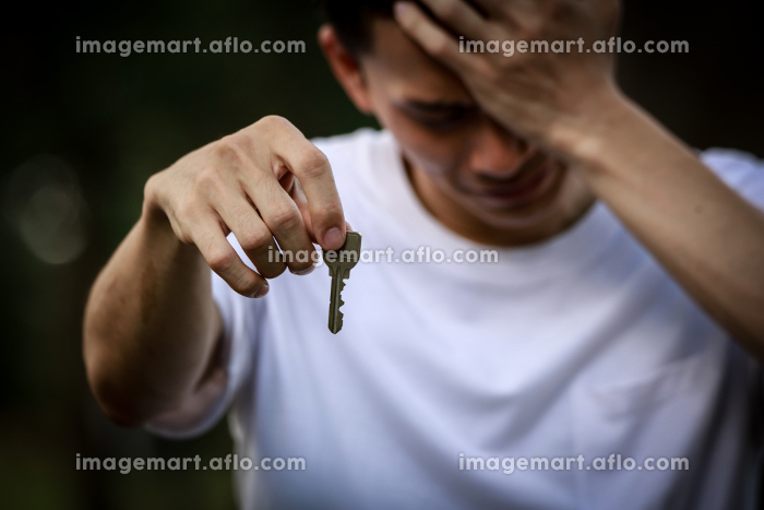 泣きながら鍵を渡す男性の販売画像