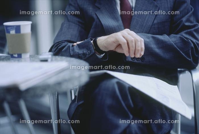 腕時計を見るビジネスマンの販売画像