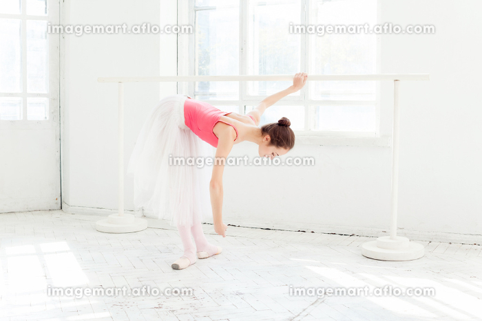 Ballerina posing in pointe shoes at white wooden pavilionの販売画像