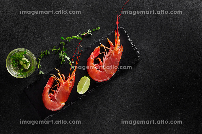 Top view of two prawns with lime, herbs and garlic sauceの販売画像