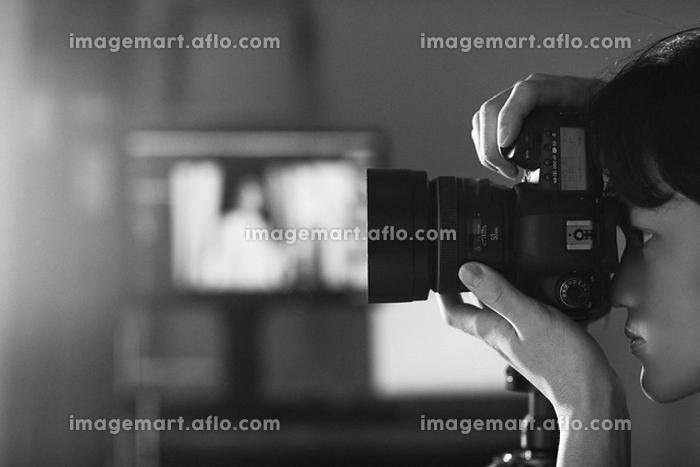 一眼レフカメラを構える日本人男性の販売画像