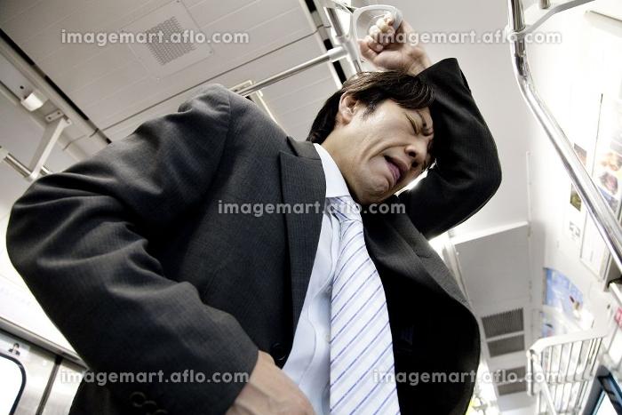 電車内で腹痛をおこすビジネスマン