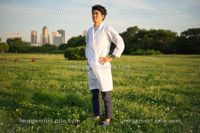 白衣姿の男性(ビル群・公園・芝生)の販売画像