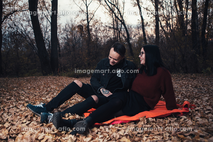 young man and young woman are sitting on a plaid in an autumn forestの販売画像