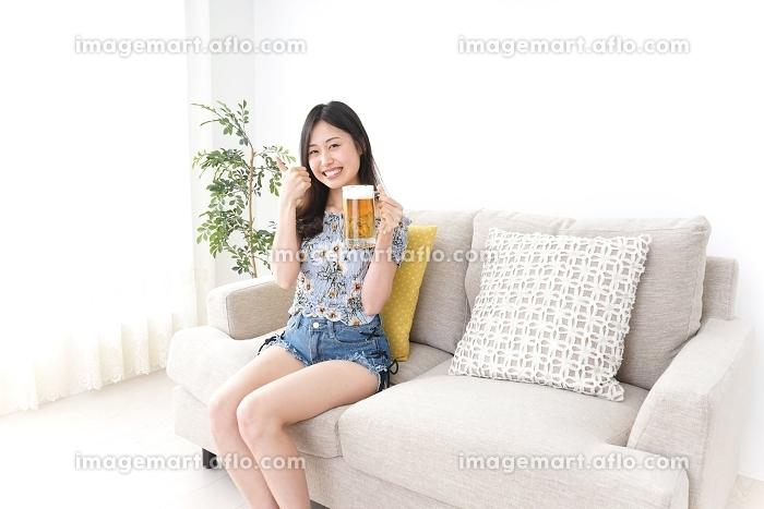 自宅でビールを飲む女性の販売画像