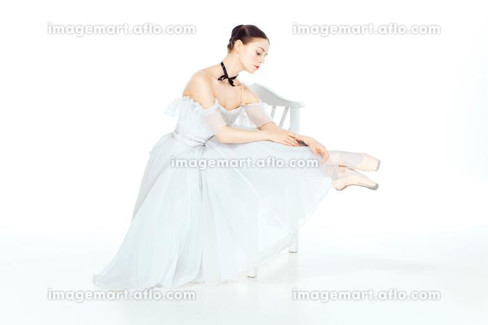 Ballerina in white dress sitting, studio background.の販売画像