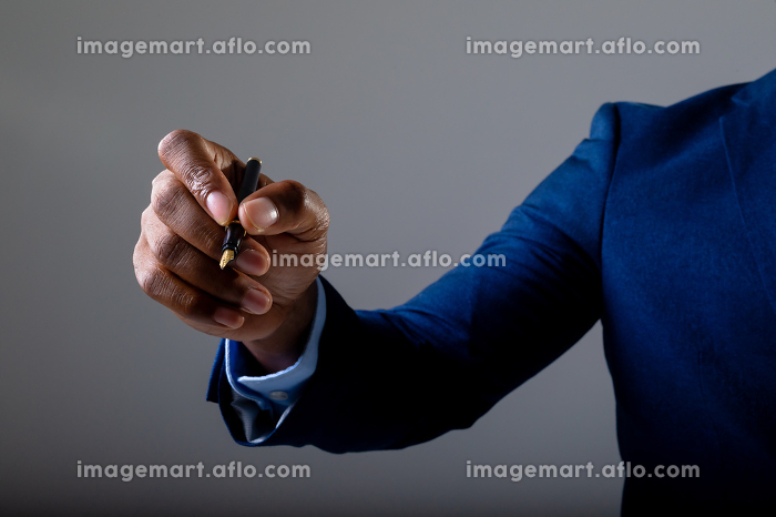 Mid section of businessman writing on invisible screen against grey background. business, professionalism and technology conceptの販売画像