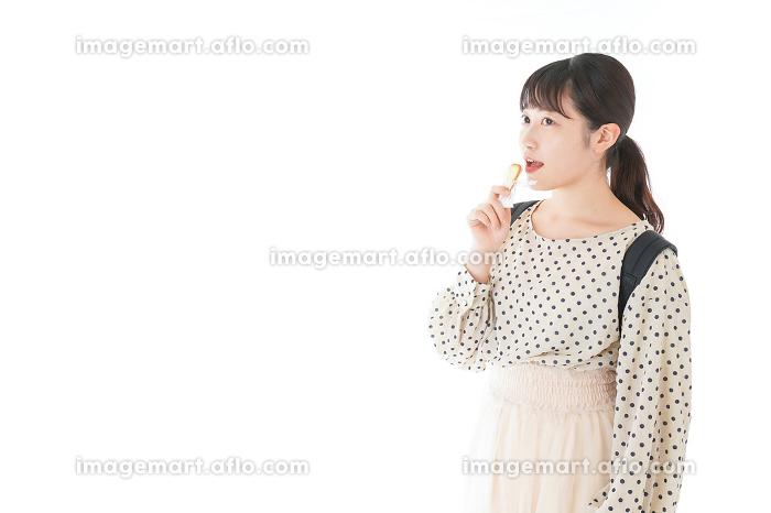 おやつを食べる若い女性の販売画像