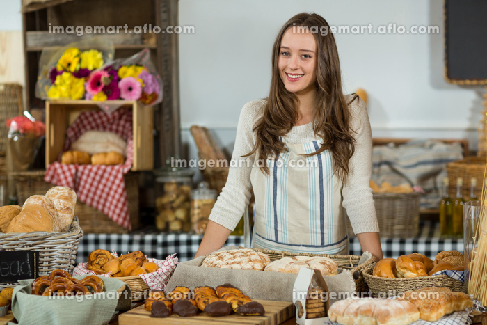 Portrait of female staff standing at counter in bake shopの販売画像