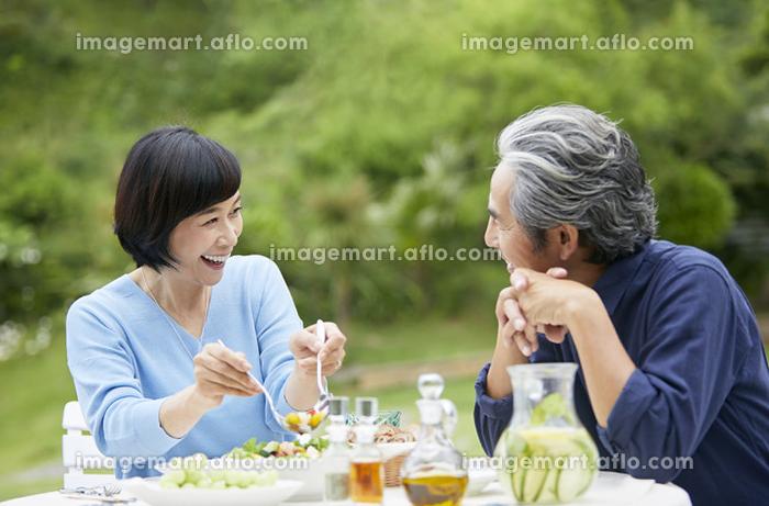 庭で食事をする日本人中年夫婦