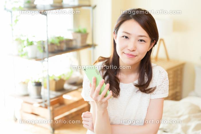部屋でスマホを見る女性の販売画像