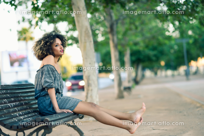Young black woman with afro hairstyle sitting on a bench in urban background moving her legs. Mixed girl wearing casual clothesの販売画像