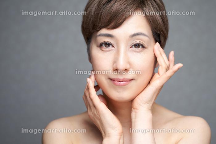 両手で顔の潤いを確かめる中年の日本人女性の販売画像