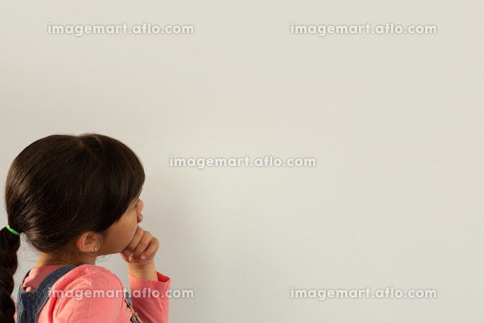 Side view of thoughtful mixed-race girl with hand on chin standing against white backgroundの販売画像