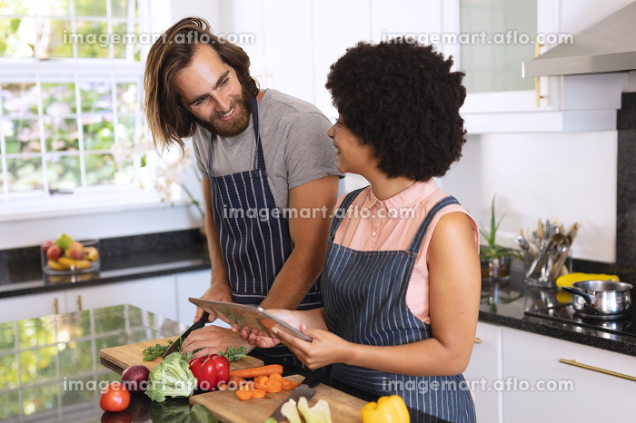 Happy diverse couple in kitchen using tablet and preparing food. staying at home in isolation during quarantine lockdown.の販売画像