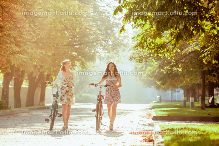 The two young girls with bicycles in parkの販売画像