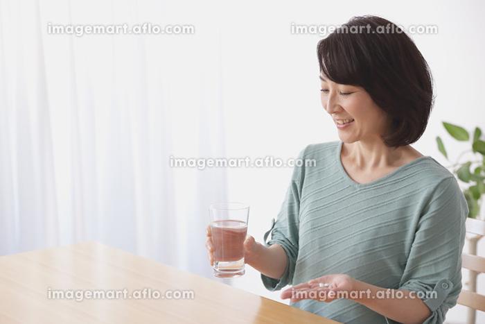 薬を飲む40代日本人女性の販売画像