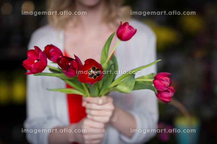 Female florist holding bunch of flower in flower shopの販売画像