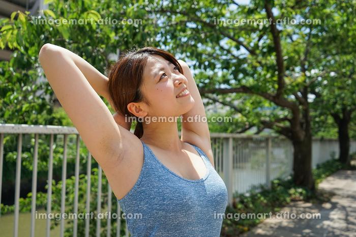 ジョギングのストレッチ準備運動をする若い女性の販売画像