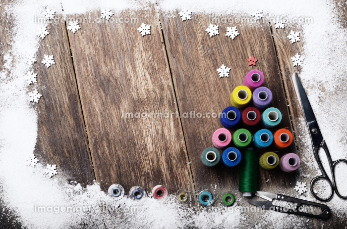 Christmas tree made of sewing spools background on wooden tableの販売画像