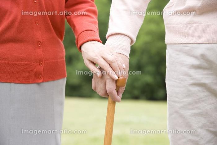 杖に手を添えあう老夫婦の手元の販売画像