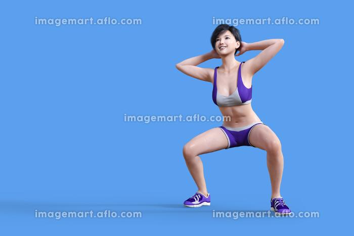 紫色のスポーティーなジャージを着た女性が元気にスクワットをするの販売画像
