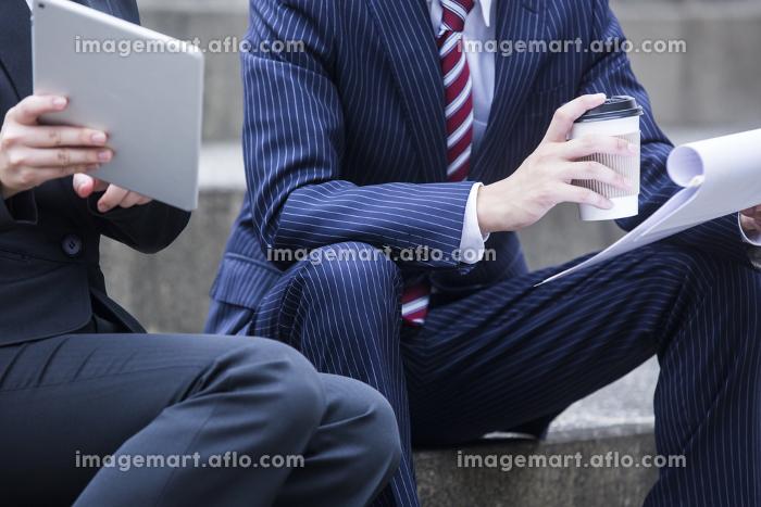 階段に座り打ち合わせをするビジネスウーマンとビジネスマンの手元