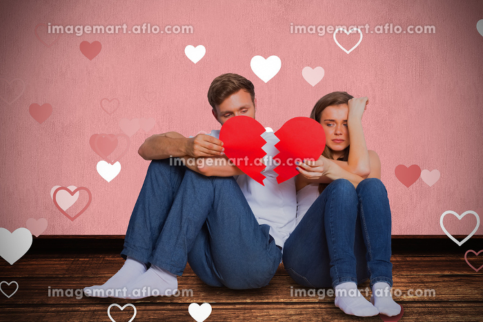 Composite image of young couple holding broken heartの販売画像