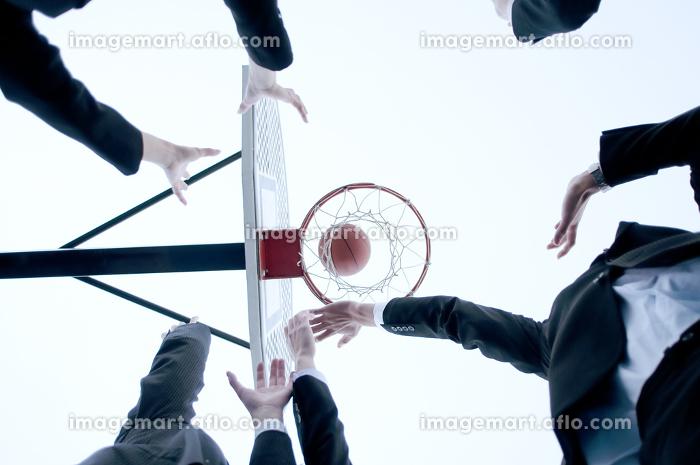 バスケットをするビジネスマンとビジネスウーマンの手元の販売画像