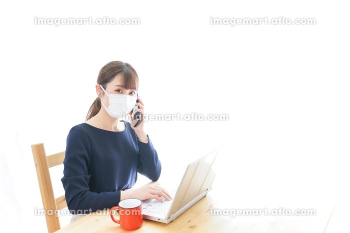 マスクをしてリモートワークをする若いビジネスウーマンの販売画像