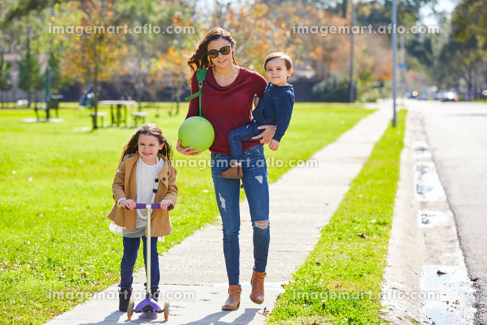 Mother daughter and son family in the park walking with ball and skate scooterの販売画像