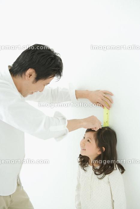 子供の背を計る父親の販売画像